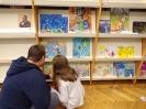 Przed wystawą prac konkursowych ojciec z córką kucając wskazują na jedną z ilustracji.