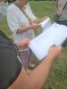 Na pierwszym planie pan w czarnej koszulce trzyma fragment tekstu, na drugim planie pani w białej bluzce trzyma fragment tekstu i wspólnie czytają.