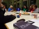 Widok na leżący na stole tomik poezji nad którym rozpościera się widok na pięć uczestniczek oglądających na laptopie archiwalny film z odczytem Paula Celana.