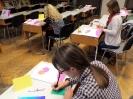 3 kobiety piszą na kolorowych kartkach, siedząc przy stolikach