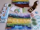 Widok z góry na rozłożone na stole elementy gry Na skrzydłach, tj. plansza do gry, kolorowe jajeczka, karty z ptakami, żetony, kostki i tekturowa budka dla ptaków