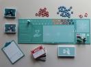Widok z góry na rozłożone na stole elementy gry Ostatnie chwile, tj. plansza do gry, na niej różnokolorowe pionki lekarzy i pielęgniarek, karty narracji i żetony funkcyjne