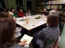 Dziesięiu uczestników wieczoru poetyckiego patrzy w kierunku mówiącego prowadzącego. Na pierwszym planie kobieta siedząca tyłem do obiektywu, trzymająca otwarty tomik wierszy.