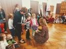 Dwoje Dzieci - chłopiec i dziewczynka - razem z Panią przedszkolanką wręczają wicedyrektor Biblioteki kwiatek i laurkę.
