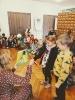 Dwoje Przedstawicieli grupy przedszkolnej 'Słoneczka' składa Pani wicedyrektor życzenia wręczając białą różę i laurkę.