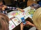 Trzy nauczycielki siedzą przy stoliku nad rozłożoną grą planszową. Jedna z nich zczytuje kod QR z żetonu do gry za pomocą aplikacji w smartfonie.