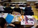 5 pań w ciemnych swetrach siedzi tyłem do obiektywu przy stolikach i wycinają szablony z kolorowego papieru.