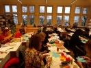 Grupa wielu osób siedzi przy stolikach, na których są materiały papiernicze takie jak: kolorowe papiery, kleje, kredki. Wycinają, kleją. W tle widoczne są duże okna.