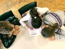 Troje uczniów pochylonych nad kartą pracy. Dziewczynka siedząca pośrodku rozwiązuje zadania.
