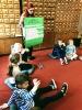 Nauczycielka otoczona siedzącymi na dywanie uczniami omawia uzupełniony przez nich arkusz z Zasadami Antyhejtowymi.
