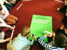 Uczniowie siedzą na dywanie wokół zielonego arkusza z Zasadami Antyhejtowymi do uzupełnienia. Dziewczynka flamastrem dopisuje na karteczce kolejną zasadę.